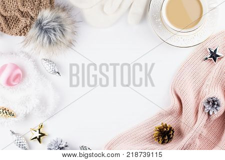 Christmas concept flat lay. Warm, cozy winter clothing and Christmas decorations frame on white background. Top view, copy space