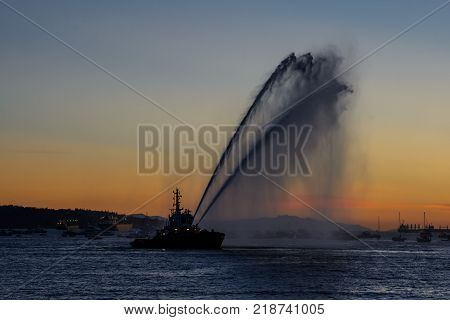 A floating modern tug boat sprays jets of water, demonstrates firefighting water cannon, sprays water as firefighter boat with the city on the background