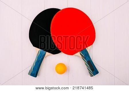 Two ping pong rocket on a white wooden background
