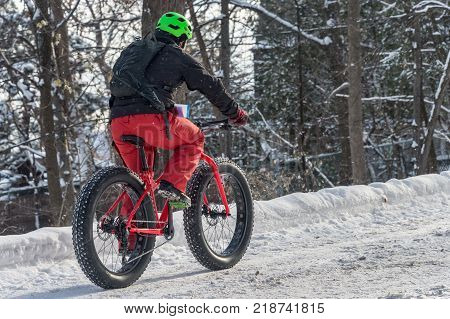 Montreal CA - 17 December 2017 A man is riding a fat tire snow bike in the Mont Royal Park.