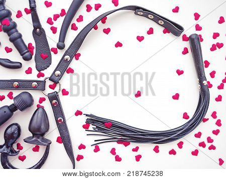 Various sex toys (dildo, butt plug, vibrator, leather harness, whip and others) are on a light background. Around the objects are scattered little red hearts. Image to the day of the holy Valentine