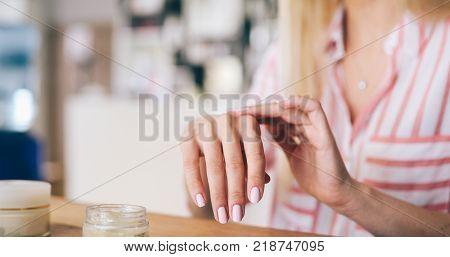 Beautiful woman applying moisturizing cream on hands