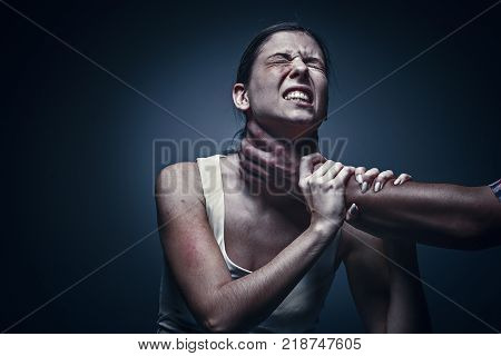 Home violence - young woman is choked by man's hand. The concept of protection from violence