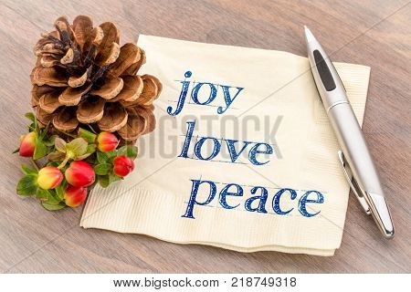 joy, love, peace concept - handwriting on a napkin with pine cone decoration