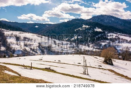 spring is comming. last days of winter landscape. rural field with weathered yellow grass covered with snow. village at the foot of the mountain ridge