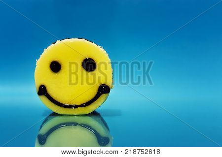 Cake in the form of an emoticon on a blue background