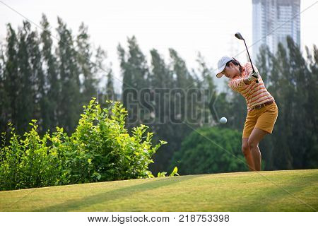 Asian woman golf player hitting chips golf ball to the hole on the green with golf club in the sunny day copy space. Lifestyle Concept.