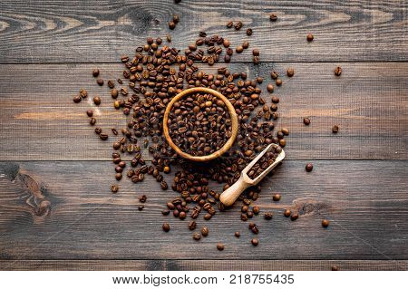 Fresh roasted coffee beans in bowl and scoop on dark wooden table top view. Coffee background