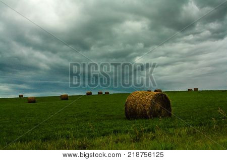 Storm clouds rolling in over hay bales, Springbank, Alberta, Canada