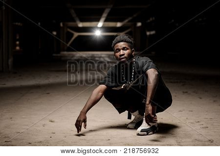 Stylish afro-american man with dreadlocks and wearing black clothes and white sneakers dancing on the background of sunset