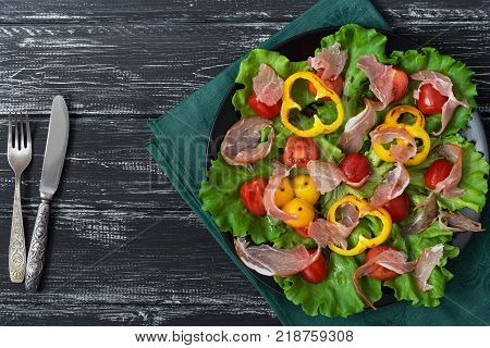 Salad with bacon and vegetables in a plate on a green napkin