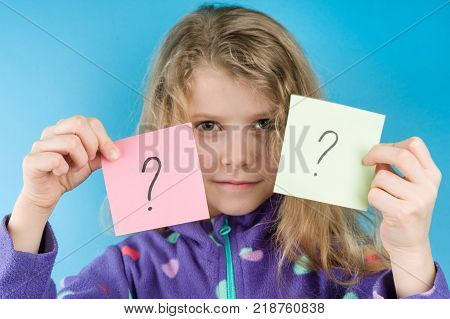 Girl holding stickers with question marks Blue background