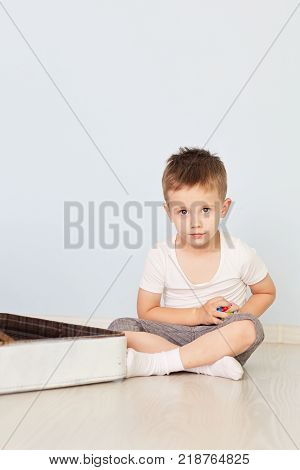 the boy sits on the white suitcase in the room. a boy plays with an open white suitcase
