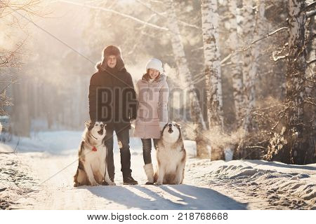 Walking with dog in winter. Lover couple is walking in snow with dog. Sun light