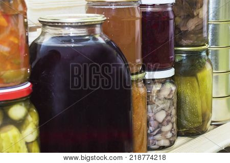 Storage shelves in pantry with homemade canned preserved fruits and vegetables.