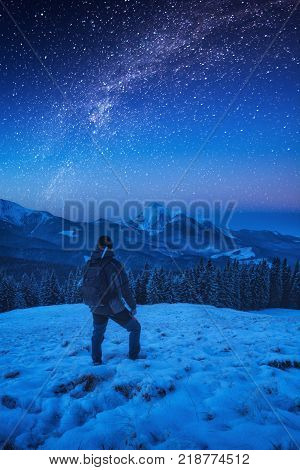 A hiker man with backpack standing on a snowy at night. Milky way in a starry sky above the mountain top.