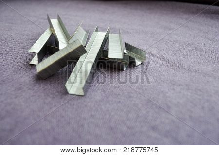 Iron metal silvery staples stacked in a heap against the background of purple cloth.