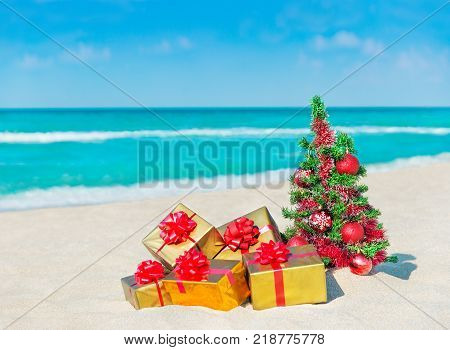 Christmas tree with red balls and golden fancy gift boxes with bows at tropical sandy beach against ocean. New Year holidays in hot countries concept square greeting card with space for your text