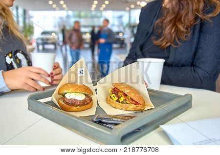 two women chatting during lunch. on a table delicious burger with fried meat cutlet, hot-dog, placed in wooden tray. In the showroom.