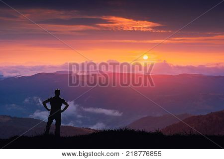 Silhouette of hiker on a hill against colorful majestic sunset in a Carrpathian mountains.