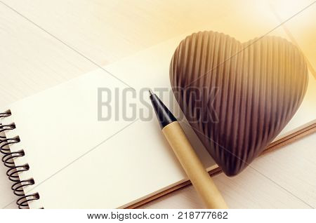 Saint Valentine's day card background, chocolate heart over empty notebook with pen, beautiful lights effect, copy space