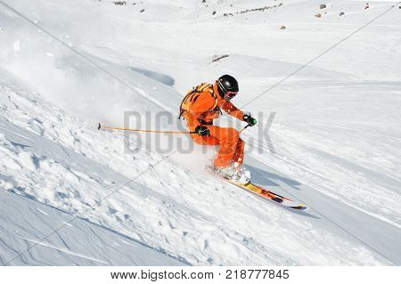 Ski athlete in a fresh snow powder rushes down the snow slope. The concept of winter ski sports