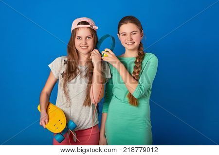 Teen girl loves to listen to the song with headphones.Laughing female friends listen to music.Two happy teen girls listening to a song in big headphones on a blue background.