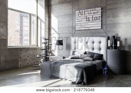 Modern empty bedroom in loft style with grey colors and wooden hand made Christmas tree with presents. Bed with grey blanket