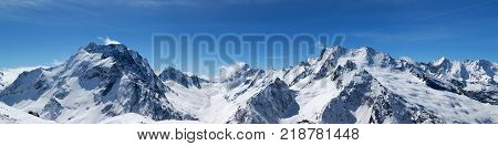 Panoramic view of snow-capped mountain peaks with mount Dombay-Ulgen and beautiful blue sky with clouds at sun windy day. Caucasus Mountains in winter region Dombay.
