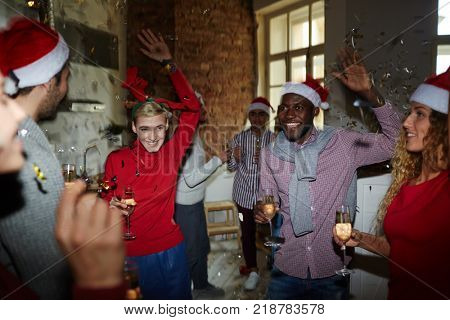 Young cheerful intercultural friends in xmas attire celebrating traditional winter holiday at home