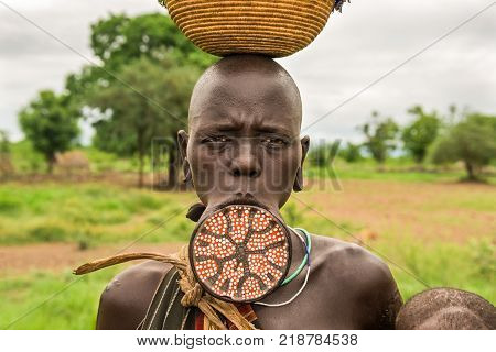 OMO VALLEY, ETHIOPIA - MAY 7, 2015 : Woman from the african tribe Mursi with a big lip plate.