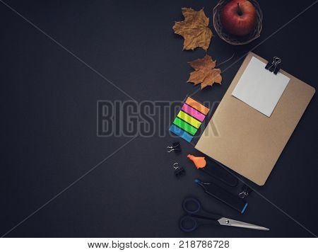 Study stuff. Education background. Aspects of education. Marker, paper, autumn leaves, notebook, scissors and an apple on the table.