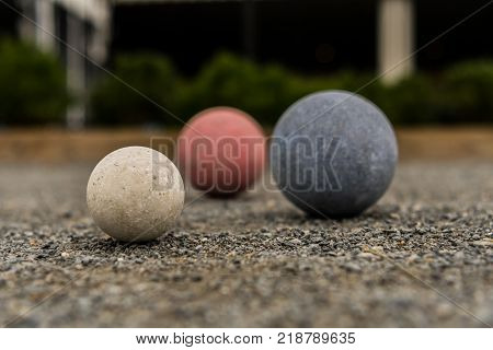 Bocce Balls on Gravel White in Focus with Red and Blue in Background