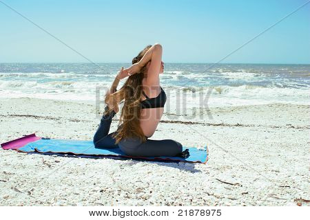 an athletic brown haired woman is doing yoga exercise woman doing yoga exercise on beach in Kapotasana or Pigeon Pose with foot in elbow and hands clasped behind her head on an empty beach at the gulf of mexico in bonita springs florida with long hair blo poster