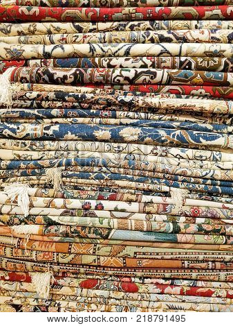 Stack Of Colorful Handmade Antique Oriental Style Rugs And Carpets Background Texture Pattern