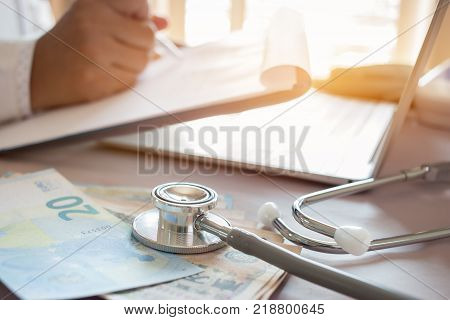 Medicine doctor's holding JPY money for Healthcare costs and fees in medical hostpital office.Focus stethoscope is acoustic device for auscultationlistening internal sounds. Healthcare budget concept