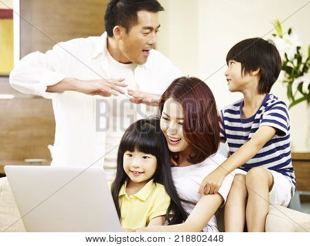 asian parents mother and father and two children son and daughter sitting on family couch using laptop computer together.