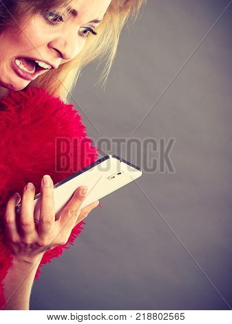 Betrayal bad relationship hurt love concept. Shocked heartbroken woman crying and looking at her phone.