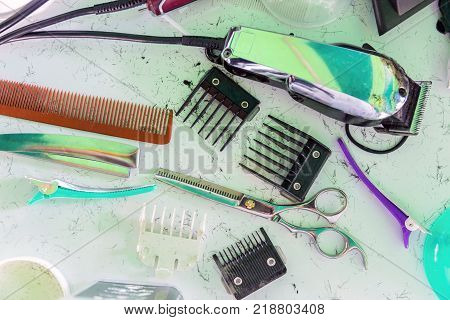A Hair clipper and scissors with comb Barber on white mess up table from hair.