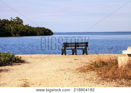 Secluded bench overlooking a large wetland marsh in the Ding Darling National Refuge on Sanibel Island Florida poster