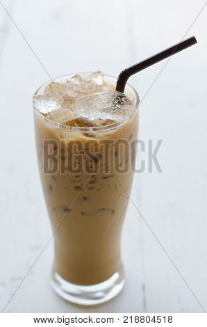 Iced coffee in a tall glass on white wooden background