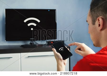connectivity between smart tv and smart phone through wifi connection. Control your TV with your smartphone. The wifi icon on the phone screen and the monitor