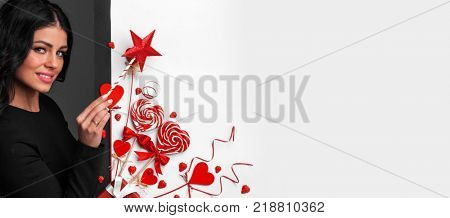 Happy woman holding magic wand and posing with Valentine's day decoration with white copy space