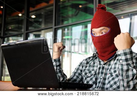 Successful masked hacker wearing a balaclava raising hands after stealing important information data with laptop. Network security and privacy crime concept.
