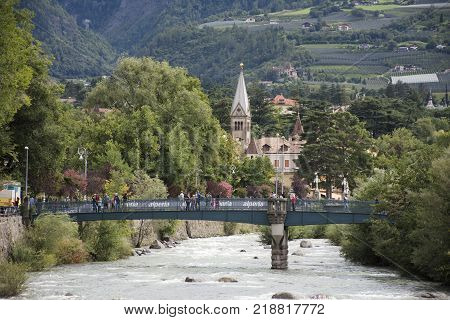 View cityscape and landscape with Italian people and foreigner travelers walking on the bridge crossover passer river at Meran city on September 2 2017 in Merano Italy