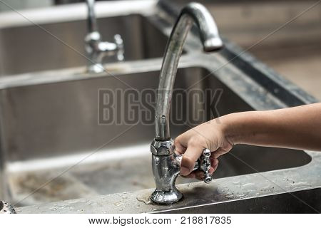 Children use their hands to open the faucet Water shortage concept.