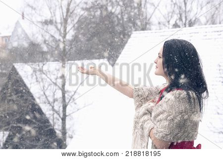 Beautiful woman catching snowflakes - Young brunette woman in a red dress and covered with a handmade shawl enjoys the snowfall and catches snowflakes with her hand.