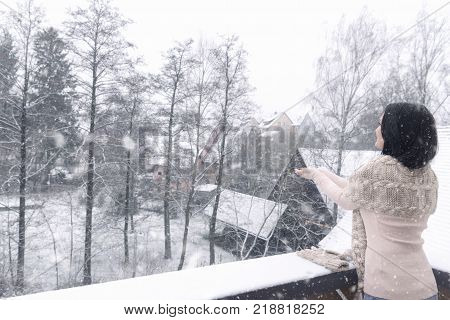 Woman catching snowflakes with both hands - Young brunette woman dressed casual stands on a balcony with her hands stretched reaching to catch the snowflakes that fall over the houses.