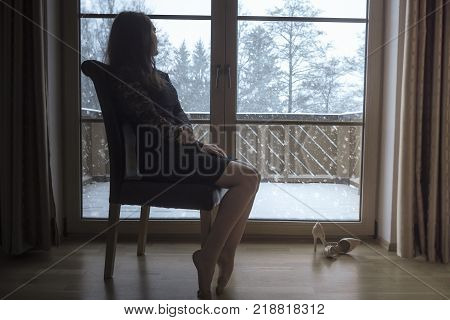 Woman sits on a chair in front of glass doors - Elegant young brunette woman wearing a black dress sitting on a chair and relaxing while looking at the snowfall through big glass doors.
