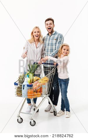 Full length portrait of a cheerful family walking with a shopping trolley full of groceries and pointing isolated over white background